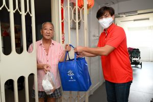 Brother Koo Wei Loon giving out a care bag to a resident